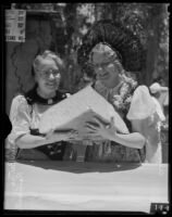 Alma Dube and Bertha Reinharth hold a hunk of Swiss cheese during the Old Folks Picnic, Los Angeles, 1935