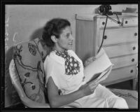Tess Slesinger, seated holding a bound typescript, Hollywood, 1935