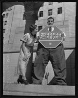 Henry Rohwer, also known as Happy Hi, holding a stop sign as punishment for a traffic violation and standing next to Lillian Brill, Los Angeles, 1935