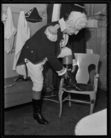 Oscar Lawler, attorney, putting on boots to complete his George Washington costume for the Los Angeles Bar Association's historical pageant, Los Angeles, 1935