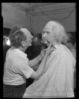Makeup artist Philip Gastrock adding the finishing touches to Judge William Hazlett's costume for the Los Angeles Bar Association's historical pageant, Los Angeles, 1935