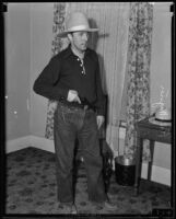Dr. Ralph Wagner, extortion victim, posing with a gun in his home, Santa Clarita, 1935