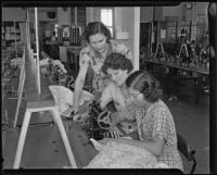 Three women using a sewing machine at the Frank Wiggins Trade School, Los Angeles, 1935