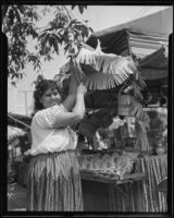 Lucy Gutierrez setting up her stand in preparation for the Founding Day Celebration on Olvera Street, Los Angeles, 1935