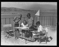 Jim Sherry, Joan Sherry, John David, and Tony Brackett working on their newspaper, Newport Beach, 1935J