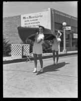 Barbara and June Murphy carrying a canoe to the Tournament of Lights, Balboa peninsula (Newport Beach), 1935