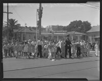 Students crossing the street with officer Ivan E. Crooks on the first day back to school, Montebello, 1935