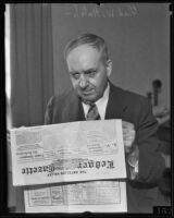 Fred W. Hatch holding newspaper, 1935