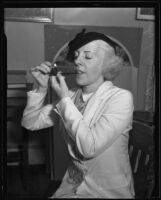 Lady Sylvia Parkyns, visiting British actress and singer, smoking a pipe, Los Angeles, 1935