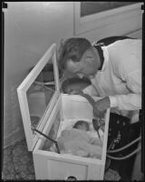 Fireman, Edwin Reed, with rescued baby, Patty Lou Williams, Los Angeles, 1935