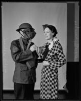 George P. Dykes and Dorothy Hawkes, holding trophy, circa 1930-1939