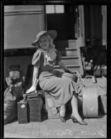 Marta Eggerth, opera singer, sits on her luggage upon arrival at the train station, Los Angeles, 1935