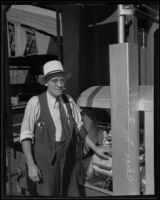 Charles M. Fuller stands next to his gold dredging invention with a cigar in his mouth, Bakersfield, 1935