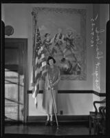 Margaret Sherlock, World War I naval veteran, poses with the American Flag, Los Angeles, 1935