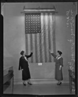 Peggy Haggerty and Marie Gore, World War I naval veterans, demonstrate how to hang the American flag perpendicularly, Los Angeles, 1935