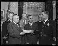 R. C. Combes, James R. Page, Joe Taylor, Robert Allen, Homer Cross, and Chief James E. Davis with the cashier's check for the Community Chest campaign, Los Angeles, 1935