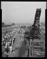Spectators look on as mechanical crane is readied to remove train wreckage, Glendale, 1935