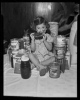 Little girl with donated goods at the Los Angeles Orphans' Home Society, Los Angeles, 1935