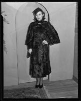 Woman models fur (?) dress, cape, and hat at the Times' fashion show, Los Angeles, 1935