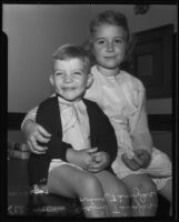 Young siblings David Tingler and Lovina Tingler sit on top of a desk, Los Angeles, 1935