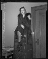 Mrs. Jeanette Brott, court witness to business suit, sits atop a file cabinet, Los Angeles, 1935