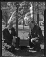 D. A. Russell and Dr. Herbert S. Johnson pose with a plaque dedicated to Benny the squirrel, Los Angeles, 1935