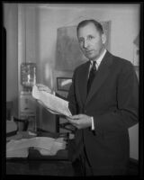 District Attorney Buron Fitts examines perjury papers, Santa Barbara, 1935