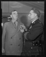 Chief of Police James Davis gives Irvin S. Cobb a badge for his honorary position, Los Angeles, 1935