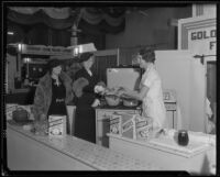 Woman serves samples behind a display at the Food and Household Show, Los Angeles, 1935