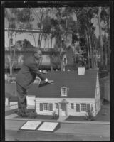 L. W. Miles touching miniature model house at the California Pacific International Exposition, San Diego, 1935