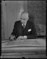 Pioneer Designer John B. Holtzclaw inspecting new drawings, Los Angeles, 1935