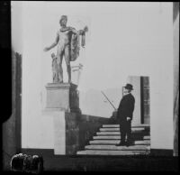 Henry E. Huntington in front of the library building of his estate pointing towards a bronze cast of the Apollo Belvedere, San Marino, (circa 1927, orig. photo.)