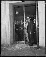 Officer William Hynes stands before broken glass door, Los Angeles, 1933