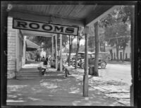 Men sitting under awnings before storefronts, Big Pine, 1927