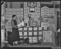 Elsie Bell stands before a display on the Times Bible Game, Los Angeles, 1934