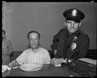 Robbery suspect Alex Smit being held at police station with officer K. E. Kurtz, Los Angeles, 1935
