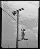 James Dooley points to burned out transformer on a utility pole, Los Angeles, ca. 1936