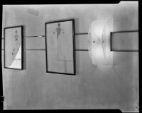 "View of two framed fashion illustrations and an art deco sconce in ""Irene LTD,"" a dress shop of designer Irene Lentz Gibbons, Los Angeles, (circa 1930?)"