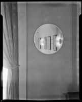 "View of a round mirror reflecting 4 framed fashion illustrations on a wall in ""Irene LTD,"" a dress shop of designer Irene Lentz Gibbons, Los Angeles, (circa 1930?)"
