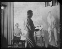 Stanley Reckless painting in the studio of his Silver Lake home as his wife (?) observes, Los Angeles, 1930-1939