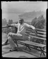 Stanley Reckless seated on a balcony of his home overlooking Silver Lake, Los Angeles, 1930-1939