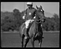 Raymond Griffith on his polo horse with his mallet raised, Los Angeles, 1931