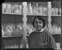 Mina Conselman standing next to her milk glass collection in her home, Eagle Rock, 1930-1939