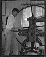 Arthur Millier operating a rolling press, Santa Monica, 1930