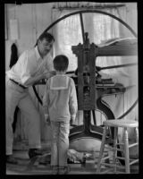 Arthur Millier operating a rolling press as a his son, Arthur, watches, Santa Monica, 1930