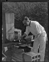 Arthur Millier cooking outdoors, Santa Monica, circa 1930-1931