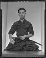 Seated Japanese man with sword, 1930-1960