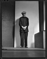 Asian-looking man standing, probably in Will Connell's photography studio, 1930-1960