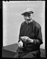 Asian-looking man seated, probably in Will Connell's photography studio, 1930-1960