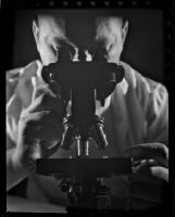 Man looking through a microscope, 1930-1960